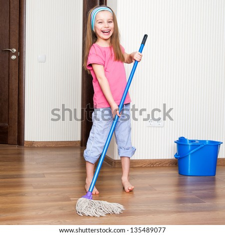 little girl washing the floor with a mop at home