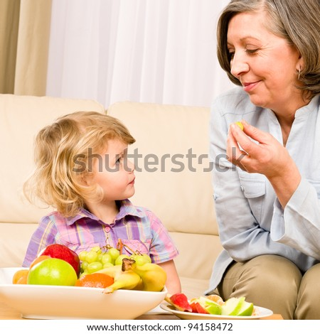 Little girl watch grandmother eat fruit relaxing on sofa