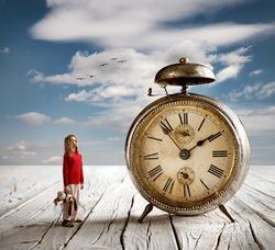 Little girl watching an old desktop alarm clock