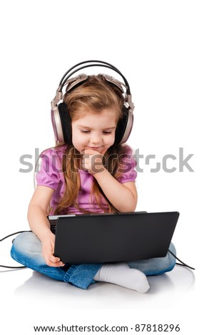 little girl watching on headphones in a laptop