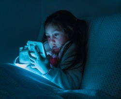little girl watching smartphone on bed, kid use phone and play game, child use mobile, addicted game and cartoon