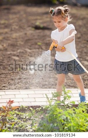 Little girl watering flowers in the garden