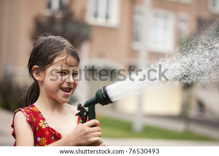 Little girl watering lawn