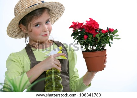 Little girl watering plant