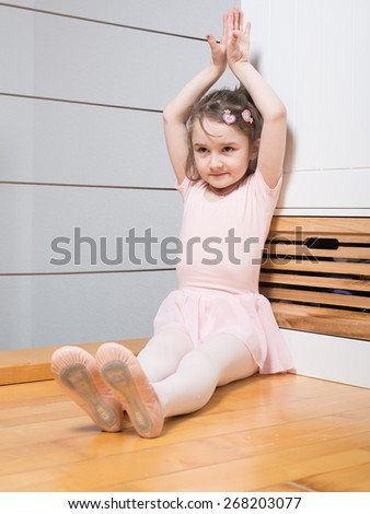 Little girl wearing a ballet dress is practicing ballet in a dance studio
