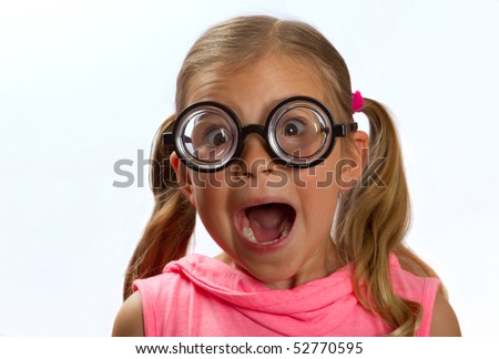Little girl wearing big round glasses and making a silly expression