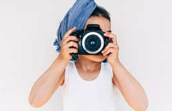 Little girl wearing blue turban on the head holding an photo camera, isolated on white background. Adorable child taking a picture with a professional camera against white background.