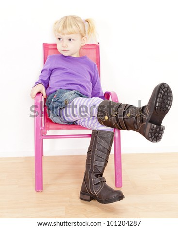 little girl wearing boots sitting on chair