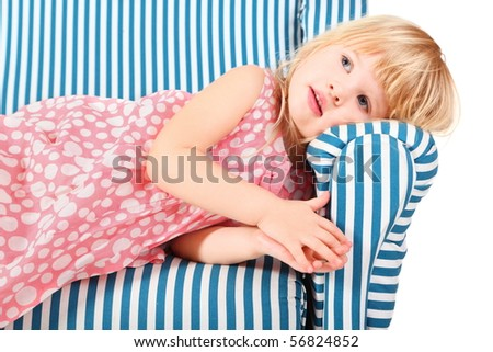 little girl wearing dress is lying on comfortable chair. isolated.