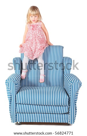 little girl wearing dress is sitting on back of striped chair. isolated.