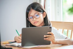 little girl wearing glasses taking class on line and using tablet for Homeschool Quarantine coranavirus pandemic New normal concept