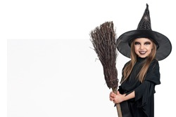 Little girl wearing halloween costume with broom and blank board on white background