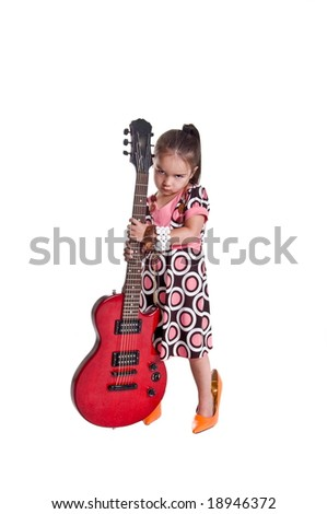 Little girl wearing mommies high heel shoes holding an electric guitar