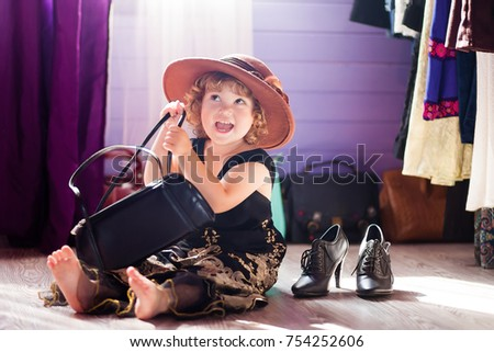 Little girl wearing mothers clothing evening dress and felt hat, lady shoes. Learning to be a woman. Growing up concept