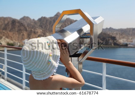 little girl wearing panama hat is looking at telescope on deck of ship
