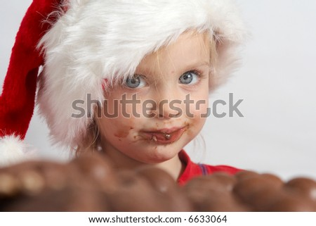 Little girl wearing red Santa hat eating chocolate