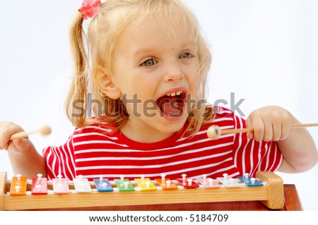 Little girl wearing striped red t-shirt playing the rainbow xylophone