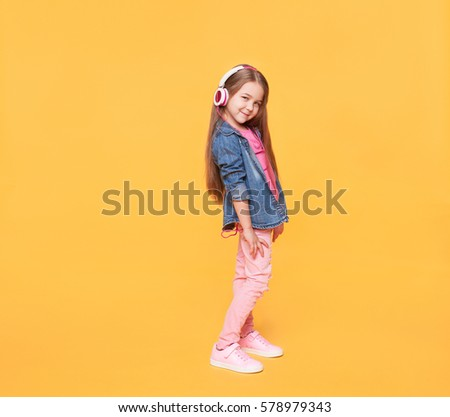 little girl wearing stylish clothes on yellow colorful background #578979343