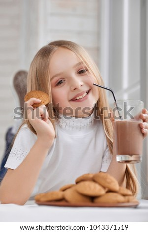Little girl wearing white sweatshirt and sneakers lies on window sill with cookie plate and delicious chocolate milk. Child has cute smile and blonde straight hair. Looks happy and pretty.
