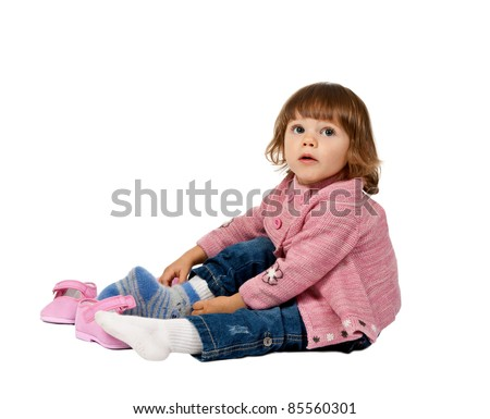 little girl wears shoes on a white floor in the studio