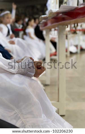 Little girl while clenching his hands during the communion