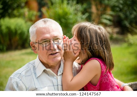 Little girl whispering her grandfather a secret to ear - outdoor in backyard