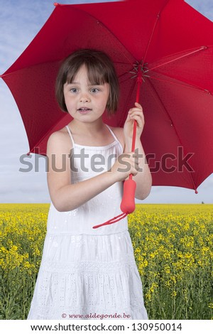 little girl wit red umbrella in front of oilseed field