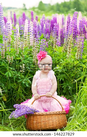 Little girl with a basket among blossoming lupines