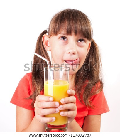 Little girl with a big glass of orange juice