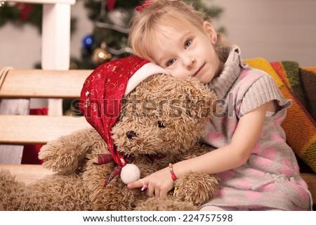 Little girl with a big teddy bear at Christmas