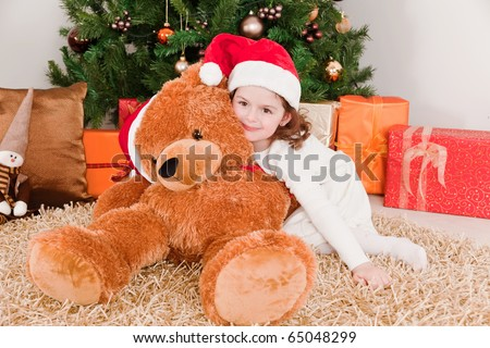 Little girl with a big teddy bear at Christmas