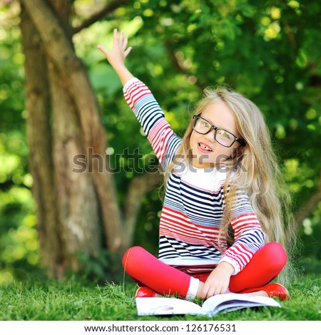 Little girl with a book in a park wearing glasses pointing at copyspace