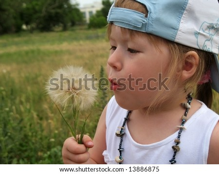 Little girl with a cap blowing a dandelion.