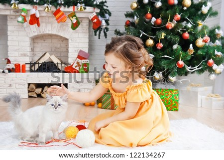 Little girl with a cat in a holiday room