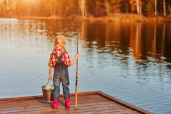 little girl with a fishing rod and a bucket came fishing and looks at the pond. Back view