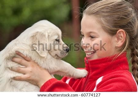 Little girl with a Golden retriever puppy - stock photo