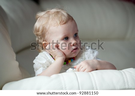 Little girl with a phone in thought settled on the couch