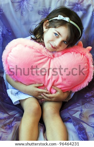 Little girl with a pink heart on violet background