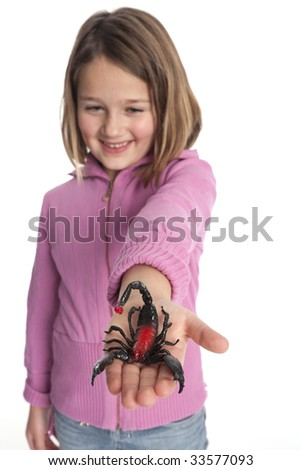Little girl with a plastic scorpion on her hand