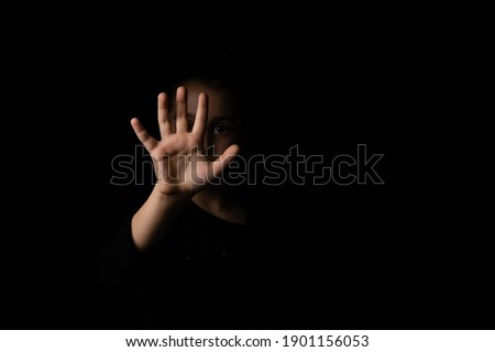 little girl with a raised hand making a stop sign gesture on a black background. Violence, harassment and child abuse prevention concept. Stock photo ©