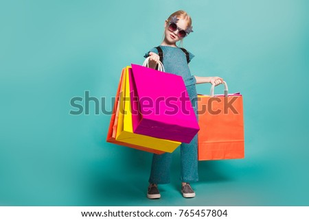 little girl with a tail in stylish clothes and sunglasses on blue background #765457804