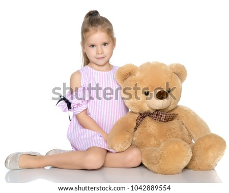Stock Photo Little girl with a teddy bear. The concept of the game, raising a child in kindergarten and in the family. Isolated on white background.