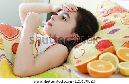 Little girl with a thermometer in bed