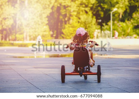 Little girl with a tricycle in the park