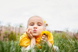 Little girl with a yellow scarf and a flower in her hair holds a yellow dandelion in her hand. The child lies in the grass and twisted her lips into a tube