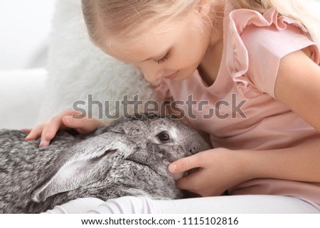 Little girl with adorable rabbit indoors