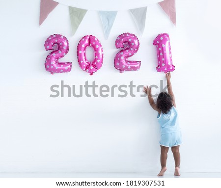 Little girl with Afro hair is arranging pink balloons for new year 2021 on the wall, new year 2021