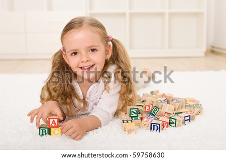 Little girl with alphabet wooden blocks playing at home