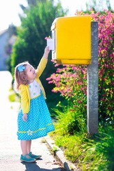 Little girl with an envelope at post office. Child sending letter. Kid throwing card into a mail box. Postal service in Germany, Europe. Delivery and shipment at outdoor mailbox.