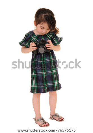 Little girl with an old camera. Studio shot.